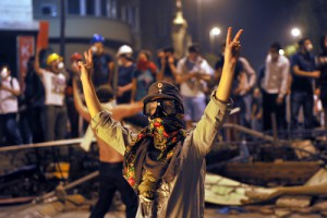 A woman protestor flashes V-sign during the clashes near Taksim in Istanbul on June 3, 2013 during a demonstration against the demolition of the park.